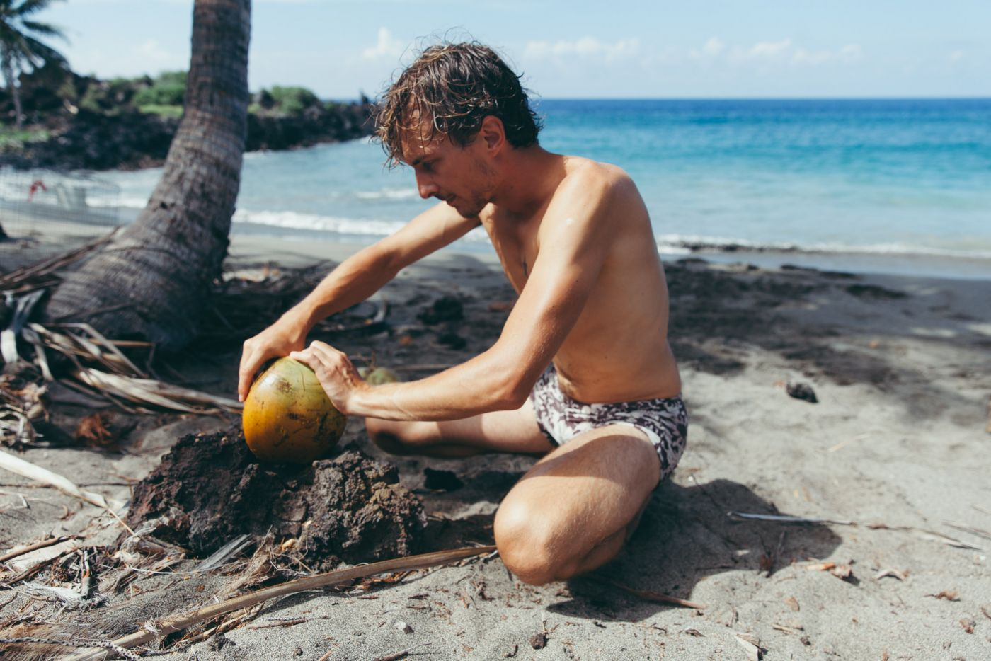 Man opening fresh coconuts, Pohue Bay Beach, Ocean View, Big Island, Hawaii