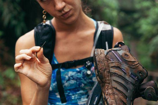 Woman pulling metal piece form shoe, Koke'e State Park, Kaua'i, Hawaii