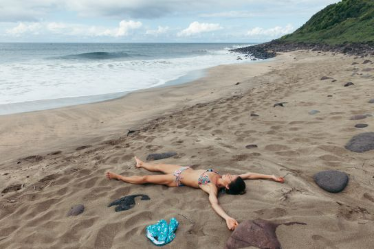 Woman laying on Kalalau Beach, Kalalau Trail, Kaua'i, Hawaii