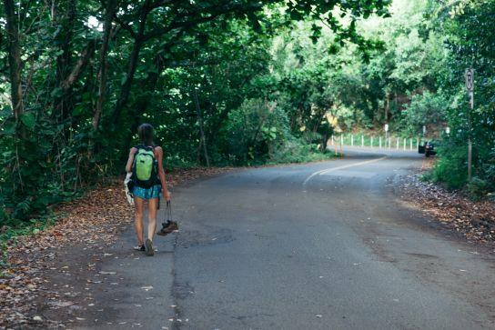 Woman walking with hiking shoes in hand, Kee Beach, Kauai, Hawaii
