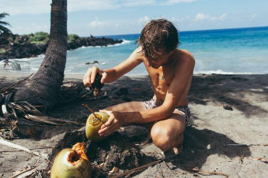 Man opening fresh cononuts, Pohue Bay Beach, Ocean View, Big Island, Hawaii