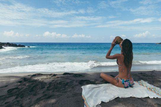Fille buvant de l'eau de coco fraiche devant la plage, Pohue Bay Beach, Ocean View, Big Island, Hawaii