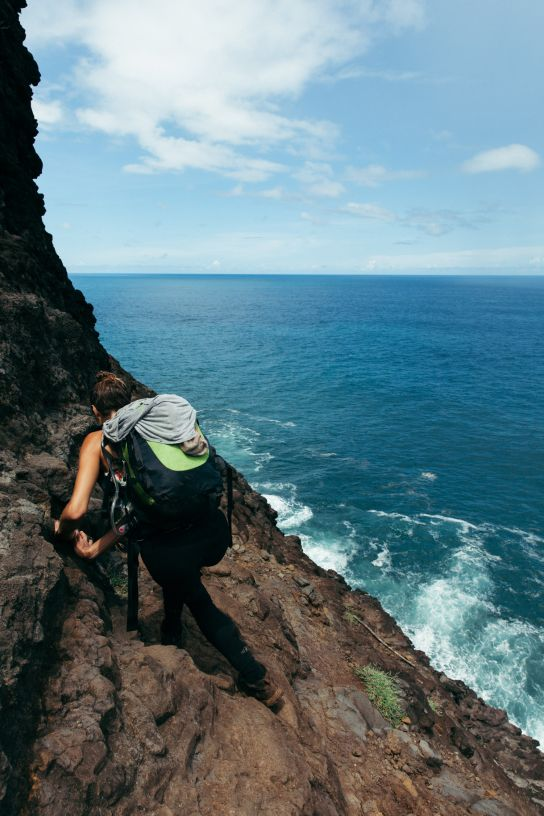 Woman hiking against a cliff over the water, Kalalau Trail, Kaua'i, Hawaii